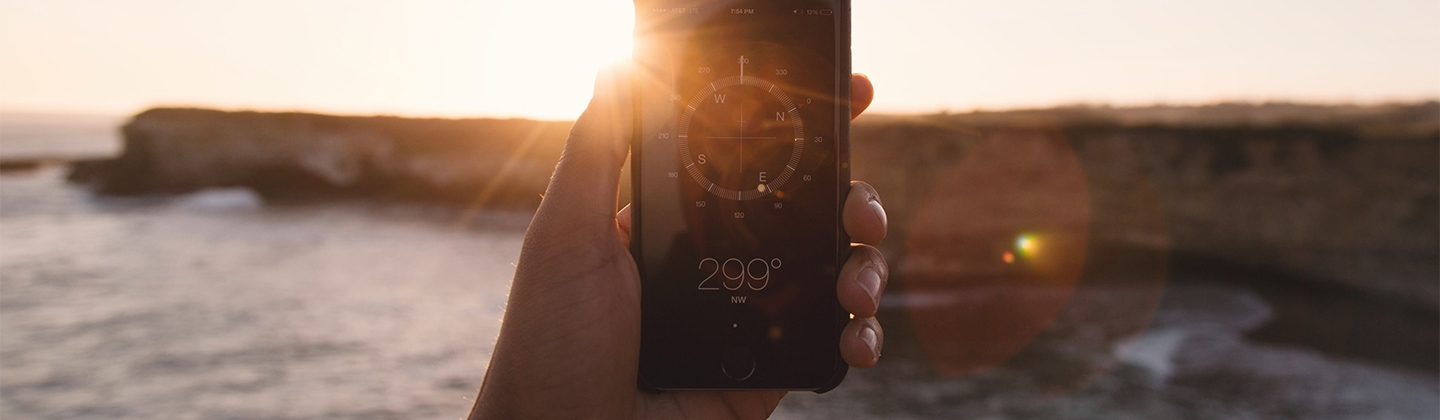 Man holding a smartphone with a compass app