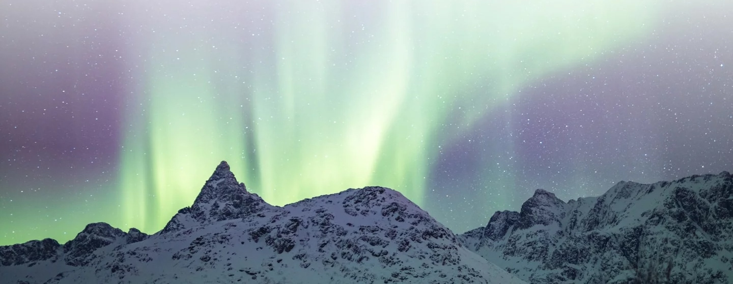 Northern lights showing over snowy mountains