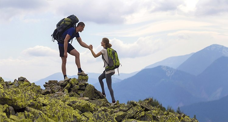 A hiker assisting another hiker up a mountain