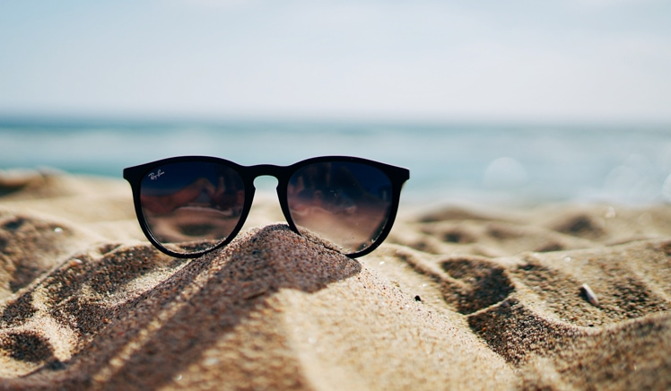 Sunglasses sitting on sand at the beach